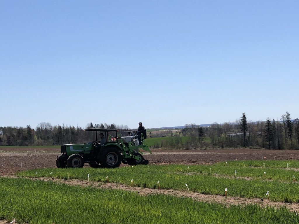 A tractor on a field with two people operating the equipment on a sunny June day.